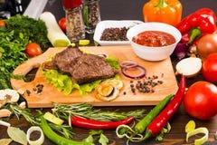 Βόειο κρέας στον ξύλινο τέμνοντα πίνακα με Salsa και Veggies Στοκ Εικόνα