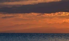 Βόρειες αιχμές βουνών Tian Shan στο πορτοκαλί φως ανατολής, ακτή λιμνών issyk-Kul, ανατολικό Κιργιστάν στοκ φωτογραφία