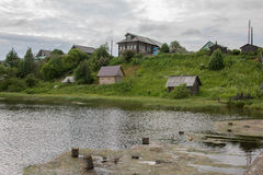Βόρειο ρωσικό χωριό Isady Θερινή ημέρα, ποταμός Emca, παλαιά εξοχικά σπίτια στην ακτή, παλαιά ξύλινη γέφυρα και αντανακλάσεις σύν Στοκ Εικόνα