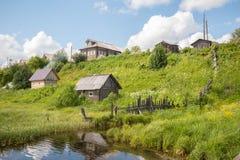Βόρειο ρωσικό χωριό Isady Θερινή ημέρα, ποταμός Emca, παλαιά εξοχικά σπίτια στην ακτή, παλαιά ξύλινη γέφυρα και αντανακλάσεις σύν Στοκ εικόνα με δικαίωμα ελεύθερης χρήσης