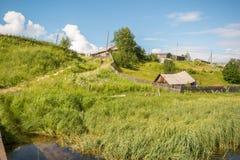 Βόρειο ρωσικό χωριό Isady Θερινή ημέρα, ποταμός Emca, παλαιά εξοχικά σπίτια στην ακτή, παλαιά ξύλινη γέφυρα και αντανακλάσεις σύν Στοκ Φωτογραφίες