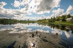 Βόρειο ρωσικό χωριό Isady Θερινή ημέρα, ποταμός Emca, παλαιά εξοχικά σπίτια στην ακτή, παλαιά ξύλινη γέφυρα και αντανακλάσεις σύν Στοκ Φωτογραφία