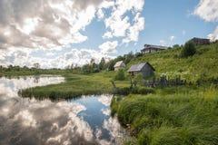 Βόρειο ρωσικό χωριό Isady Θερινή ημέρα, ποταμός Emca, παλαιά εξοχικά σπίτια στην ακτή, παλαιά ξύλινη γέφυρα και αντανακλάσεις σύν Στοκ εικόνες με δικαίωμα ελεύθερης χρήσης