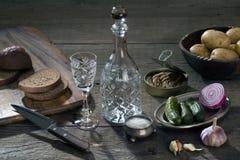 Βότκα σε μια καράφα κρυστάλλου και ποικίλα προϊόντα για τα πρόχειρα φαγητά στοκ φωτογραφία
