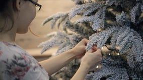 Βλάστηση από την πίσω ασιατική σφαίρα παιχνιδιών γυναικών κρεμώντας στο δέντρο απόθεμα βίντεο