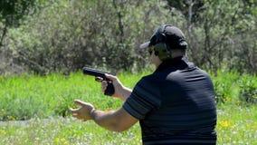 Βλαστοί ατόμων με ένα πυροβόλο όπλο στους στόχους στη σειρά πυροβολισμού απόθεμα βίντεο