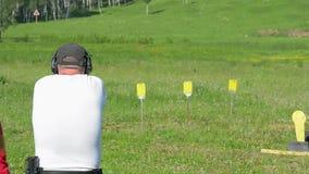 Βλαστός ατόμων με ένα πυροβόλο όπλο στους στόχους στη σειρά πυροβολισμού απόθεμα βίντεο