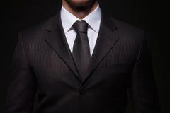 Επιχειρηματίας που στέκεται στο σκοτεινό υπόβαθρο Στοκ φωτογραφία με δικαίωμα ελεύθερης χρήσης