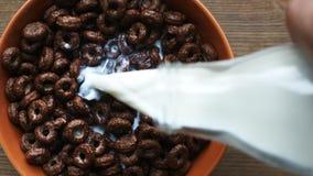 Γάλα από την αργή έκχυση μπουκαλιών στο κύπελλο με τα δαχτυλίδια σοκολάτας φιλμ μικρού μήκους