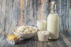 Γάλα σε ένα βουτύρου ξινό τυρί εξοχικών σπιτιών κρέμας μπουκαλιών και ένα ποτήρι του γάλακτος σε ένα πράσινο υπόβαθρο στοκ εικόνες