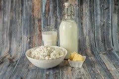 Γάλα σε ένα βουτύρου τυρί εξοχικών σπιτιών μπουκαλιών και ένα ποτήρι του γάλακτος σε ένα ξύλινο υπόβαθρο στοκ φωτογραφίες