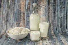 Γάλα σε ένα ξινό τυρί εξοχικών σπιτιών κρέμας μπουκαλιών και ένα ποτήρι του γάλακτος σε ένα ξύλινο υπόβαθρο στοκ φωτογραφίες με δικαίωμα ελεύθερης χρήσης