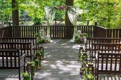 γάμος ιδιοτήτων γάμος λουλουδιών τελετής νυφών Οι άσπροι στυλοβάτες ενός γάμου σχηματίζουν αψίδα, διακοσμημένος με τα λουλούδια,  Στοκ Εικόνες