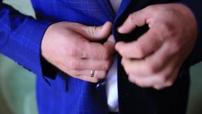 Γάμος, κινηματογράφηση σε πρώτο πλάνο, χέρια του νεόνυμφου που κουμπώνει το σακάκι απόθεμα βίντεο