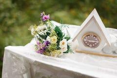 γάμος κορδελλών πρόσκλησης λουλουδιών κομψότητας λεπτομέρειας διακοσμήσεων ανασκόπησης ρολόι, ανθοδέσμη στον πίνακα Στοκ φωτογραφίες με δικαίωμα ελεύθερης χρήσης