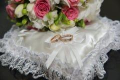 Γάμος δύο δαχτυλιδιών, μαξιλάρι με μορφή μιας καρδιάς, μια ανθοδέσμη των κόκκινων και άσπρων τριαντάφυλλων Στοκ Εικόνα