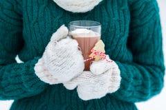 Γάντια κοριτσιών που κρατούν το καυτό κακάο Χριστουγέννων με λειώνοντας marshmallows στο φλυτζάνι γυαλιού Στοκ φωτογραφία με δικαίωμα ελεύθερης χρήσης