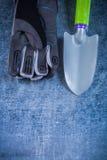 Γάντια προσωπικού φτυαριών κηπουρικής χάλυβα στη μεταλλική κατακόρυφο επιφάνειας Στοκ Φωτογραφία