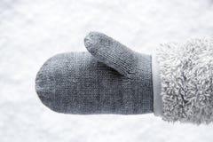 Γάντι μαλλιού με το δέρας, χιόνι στο υπόβαθρο στοκ εικόνα