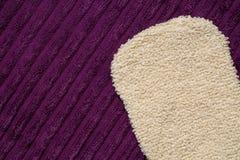 Γάντι μασάζ στην πορφυρή πετσέτα λουτρών Στοκ Εικόνες