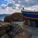 Γάτα στη ζωηρόχρωμη βάρκα στο ηλιοβασίλεμα σε Marsaxlokk, Μάλτα στοκ φωτογραφία με δικαίωμα ελεύθερης χρήσης