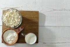 Γάλα, ξινή κρέμα, τυρί εξοχικών σπιτιών στα φλυτζάνια σε έναν πίνακα στοκ εικόνες με δικαίωμα ελεύθερης χρήσης