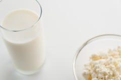Γάλα σε ένα γυαλί, τυρί εξοχικών σπιτιών σε ένα κύπελλο, σε έναν άσπρο πίνακα, μέσα Στοκ Εικόνες