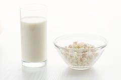 Γάλα σε ένα γυαλί, τυρί εξοχικών σπιτιών σε ένα κύπελλο, σε έναν άσπρο πίνακα, μέσα Στοκ Φωτογραφίες