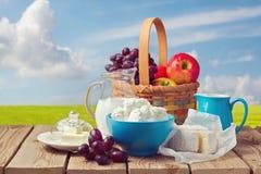 Γάλα, τυρί εξοχικών σπιτιών, βούτυρο και καλάθι φρούτων πέρα από το υπόβαθρο λιβαδιών Εβραϊκός εορτασμός Shavuot διακοπών Στοκ Εικόνες