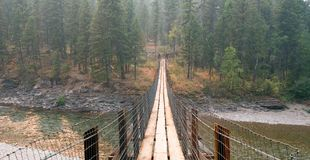 Γέφυρα αναστολής πέρα από το Flathead ποταμό στον επισημασμένο σταθμό δασοφυλάκων αρκούδων/Campground στη Μοντάνα ΗΠΑ Στοκ φωτογραφία με δικαίωμα ελεύθερης χρήσης