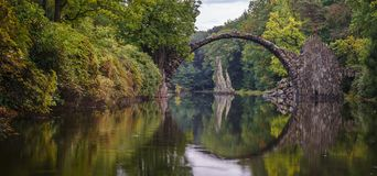 Γέφυρα αψίδων σε Kromlau, Σαξωνία, Γερμανία Ζωηρόχρωμο φθινόπωρο στο μικρόβιο στοκ φωτογραφία με δικαίωμα ελεύθερης χρήσης
