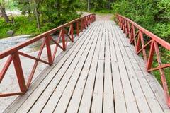 Γέφυρα με τα κόκκινα κιγκλιδώματα πέρα από το ρεύμα το καλοκαίρι Στοκ Εικόνα