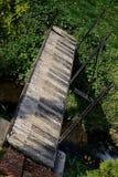 Γέφυρα πέρα από το ρεύμα νερού κήπων που χρωματίζεται ως κλειδιά πιάνων Στοκ εικόνα με δικαίωμα ελεύθερης χρήσης