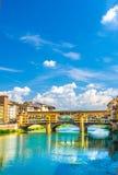 Γέφυρα πετρών Vecchio Ponte με τα ζωηρόχρωμα σπίτια κτηρίων πέρα από το μπλε ποταμών Arno που απεικονίζει το νερό στο ιστορικό κέ στοκ φωτογραφία με δικαίωμα ελεύθερης χρήσης