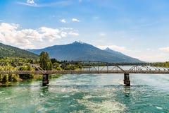 Γέφυρα ραγών πέρα από τον ποταμό με το υπόβαθρο Καναδάς βουνών στοκ εικόνες