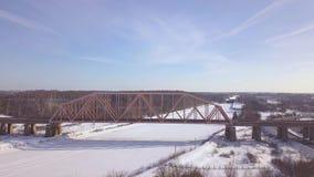 Γέφυρα σιδηροδρόμων αναστολής για την κυκλοφορία τραίνων πέρα από τον παγωμένο ποταμό στην εναέρια άποψη χειμερινών τοπίων Κυκλοφ φιλμ μικρού μήκους