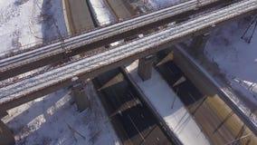 Γέφυρα σιδηροδρόμων αναστολής επάνω από τη χειμερινή εθνική οδό και κυκλοφορία αυτοκινήτων στο χιονώδες οδικό εναέριο τοπίο Γέφυρ φιλμ μικρού μήκους
