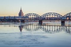 Γέφυρα σιδηροδρόμων πέρα από τον παγωμένο ποταμό το χιονώδη χειμώνα Ρήγα κατά τη διάρκεια του ήλιου Στοκ Εικόνα
