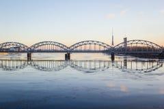 Γέφυρα σιδηροδρόμων πέρα από τον παγωμένο ποταμό το χιονώδη χειμώνα Ρήγα κατά τη διάρκεια του ήλιου Στοκ εικόνες με δικαίωμα ελεύθερης χρήσης