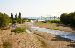 Γέφυρα σιδηροδρόμων πέρα από τον ποταμό, που ρέει στη θάλασσα στοκ φωτογραφία με δικαίωμα ελεύθερης χρήσης