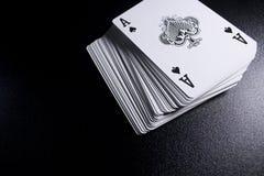 γέφυρα σωρών καρτών πόκερ άσσων στο σκοτεινό υπόβαθρο Στοκ Φωτογραφίες