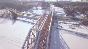 Γέφυρα τραίνων αναστολής μέσω του χειμερινού ποταμού και κυκλοφορία αυτοκινήτων στη χιονώδη εναέρια άποψη εθνικών οδών Γέφυρα σιδ απόθεμα βίντεο