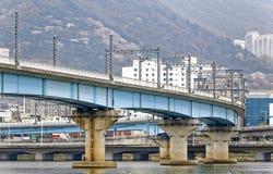 Γέφυρα τραίνων πέρα από το υπόβαθρο ποταμών και πόλεων σε busan Στοκ Εικόνα