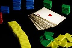 Γέφυρα των καρτών πόκερ δίπλα στα χρωματισμένα πλαστικά τσιπ στοκ φωτογραφίες