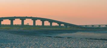 Γέφυρες που διασχίζουν ένα έλος κοντά σε μια παραλία στο ηλιοβασίλεμα στοκ φωτογραφίες
