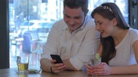Γέλια γυναικών που εξετάζουν το τηλέφωνο ανδρών ` s απόθεμα βίντεο
