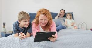 Γέλιο μητέρων και γιων που χρησιμοποιεί τα αστεία βίντεο ρολογιών υπολογιστών ταμπλετών που βρίσκονται στο κρεβάτι στην οικογένει απόθεμα βίντεο