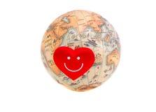 Γήινη σφαίρα με τη μικρή κόκκινη καρδιά Στοκ Εικόνες