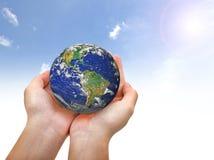 Γήινος πλανήτης στο θηλυκούς χέρι και το μπλε ουρανό Στοκ εικόνα με δικαίωμα ελεύθερης χρήσης