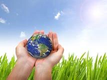 Γήινος πλανήτης στο θηλυκούς χέρι και το μπλε ουρανό Στοκ Εικόνα